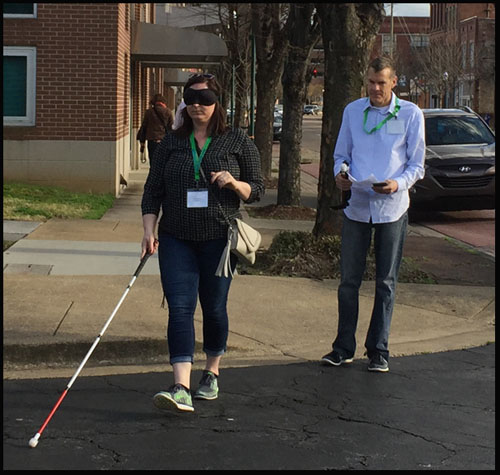 Photo shows a woman with a blindfold crossing a street while a man behind her carries his instructions.  Both are wearing green lanyards with name tags from the conference.