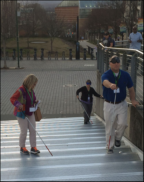 Photo shows 3 people with canes walking from a plaza up a long flight of stairs.  Two are wearing blindfolds.