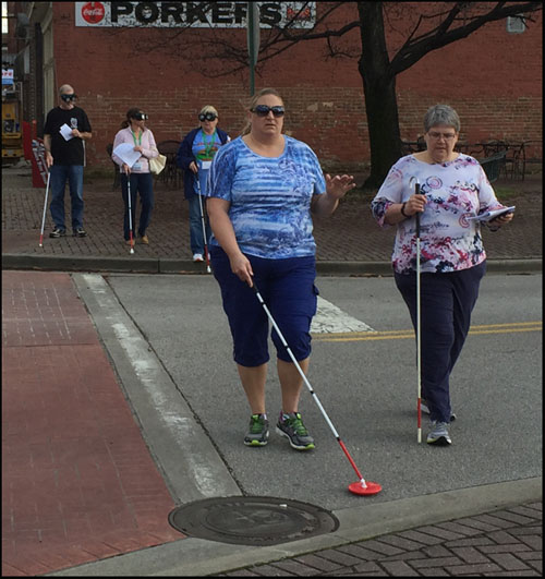 Photo shows two people crossing a narrow street with a stop sign.  One is blindfolded and using a cane.  At the corner behind them are 3 more people wearing vision simulators and using canes.