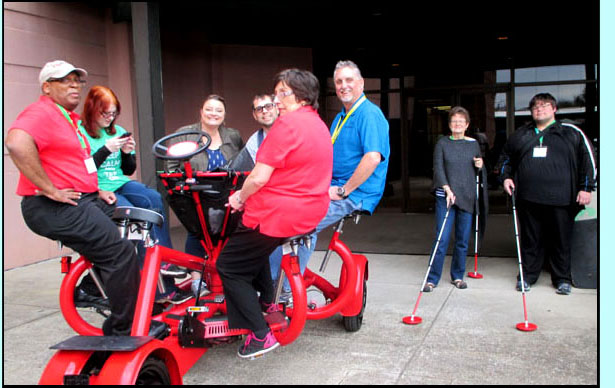 Picture shows people sitting in a circle on a 4-wheeled bicycle, each person has their feet on bicycle pedals.  Beside them are a man and a woman, each holding a cane with a red disk at the bottom, about 10 inches across.