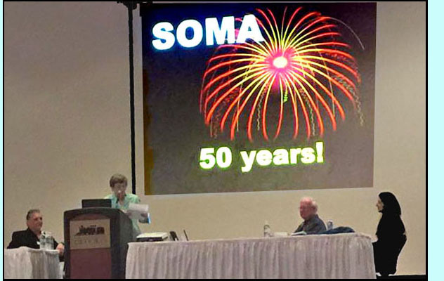 Photo shows people on a large stage with a podium and table, the slide behind them shows fireworks and says 'SOMA 50 years!'