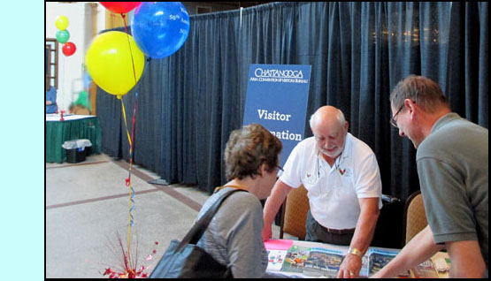 Two pictures show a man behind a small table showing people maps and brochures.  One photo has a man with two children, the other has a man and a woman looking at the map.