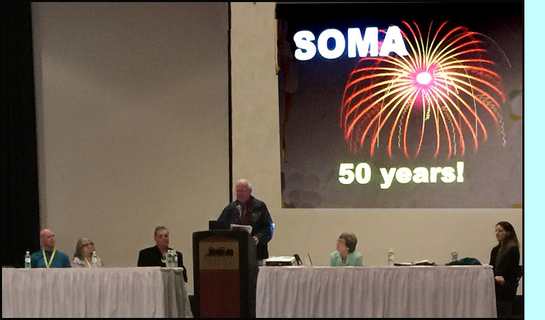 Picture shows people on a large stage with a podium and table, the slide behind them shows fireworks and says 'SOMA 50 years!'