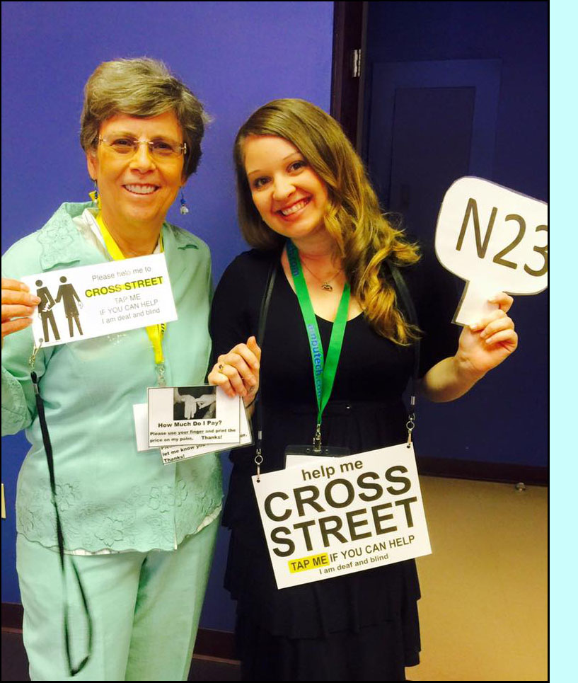 Photo shows Dona wearing a light green pants suit and Tara wearing a black dress, each are holding cards and signs and smiling at the camera.