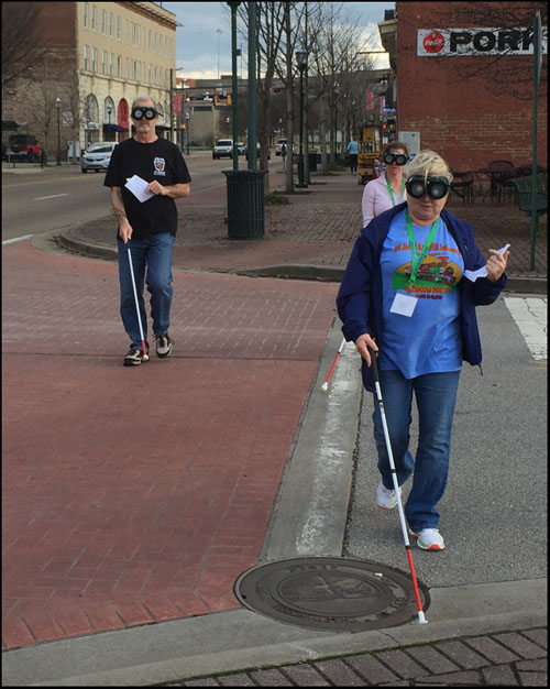 Photo shows 3 people wearing vision simulators and using a cane while crossing a street with a stop sign.