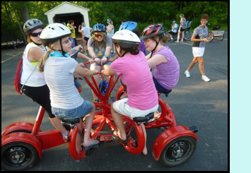 Photo shows 7 young teenage girls on the 4-wheeled red bicycle sitting in a circle and holding onto a circular bar in the middle of them.  They are in a parking lot at a park, and other people are smiling as they walk by and look at the girls.