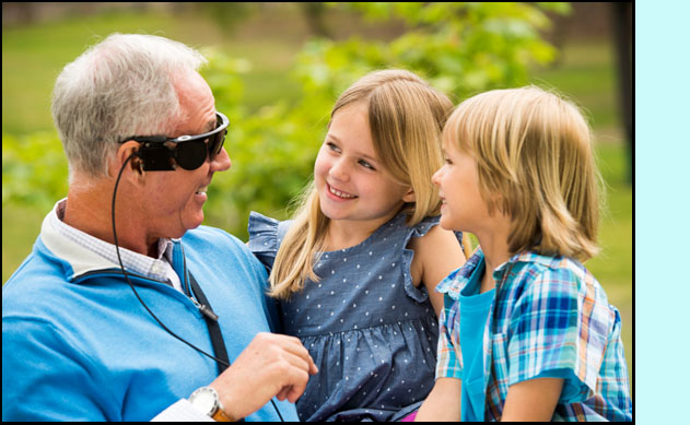 Photo shows a man smiling and looking at two children that he is holding on his lap.  He is wearing what looks like wrap-around sunglasses with a cord coming down to his shirt.