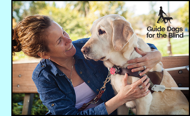 photo shows a woman sitting by a dog who is wearing a guide dog harness.  The woman is smiling broadly and looking at the dog while holding her arms around the dog's chest.