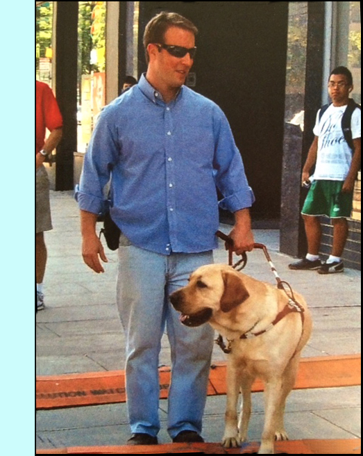 photo shows a man walking along a downtown sidewalk with a dog who is looking and seems to be turning to their right.