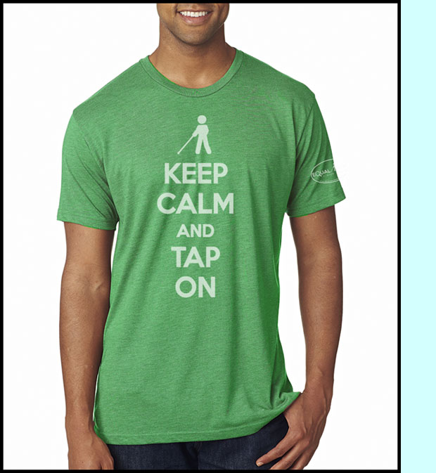 Photo shows a soft green T-shirt with a sillouette of a cane user saying 'Keep Calm and Tap On'