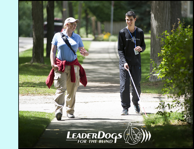 photo shows a young man walking with a cane along a sidewalk next to an instructor. She is talking to him and he is smiling.