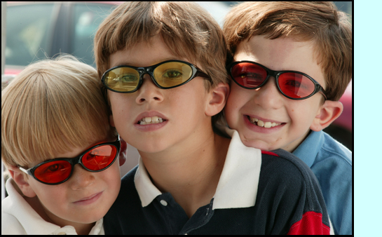 photo shows 3 young children posing together wearing sunglasses tinted in different colors.