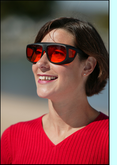 photo shows a woman smiling and red-tinted sunglasses with top and side shields.
